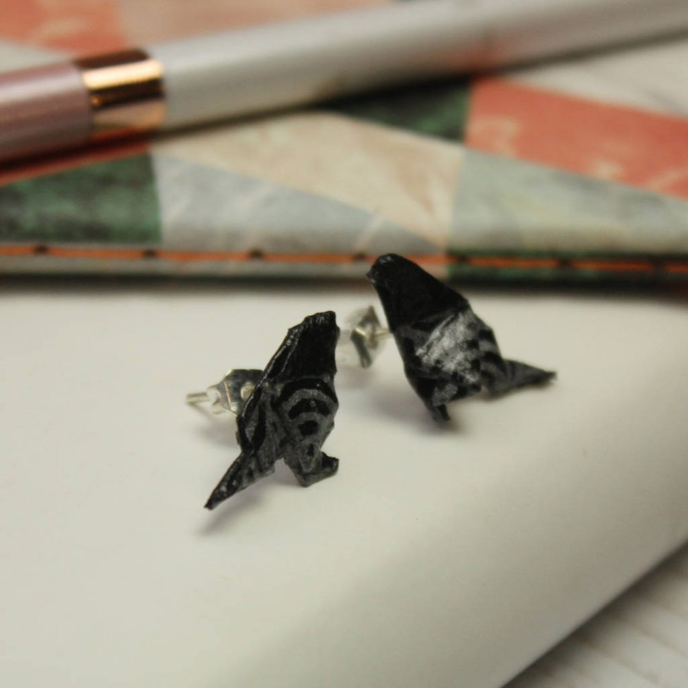 Side view of hand folded origami bird earrings, in black and silver waves. Hand made by the Origami Boutique in London.