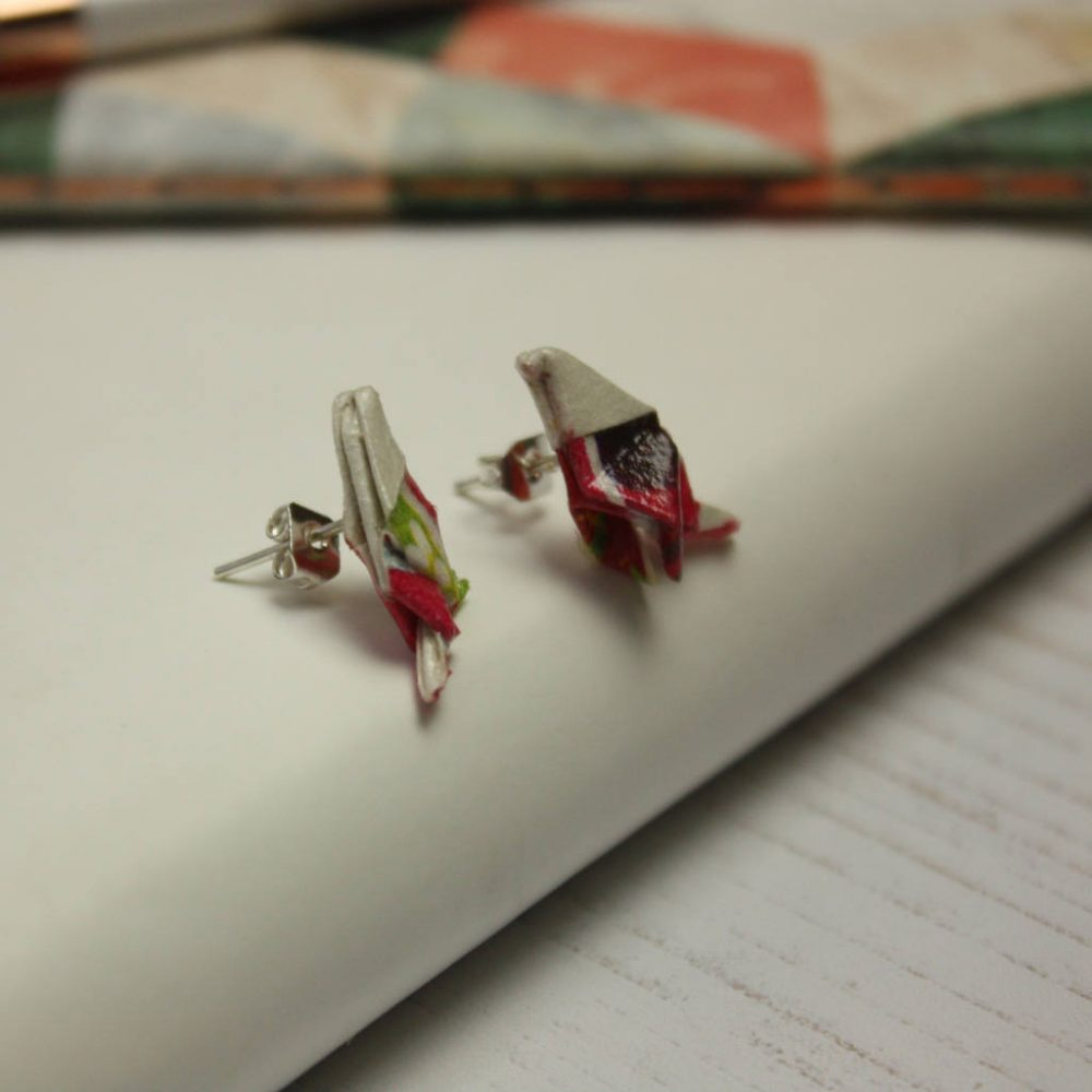 Side view of paper bird earrings in carnival pattern, by the origami boutique.