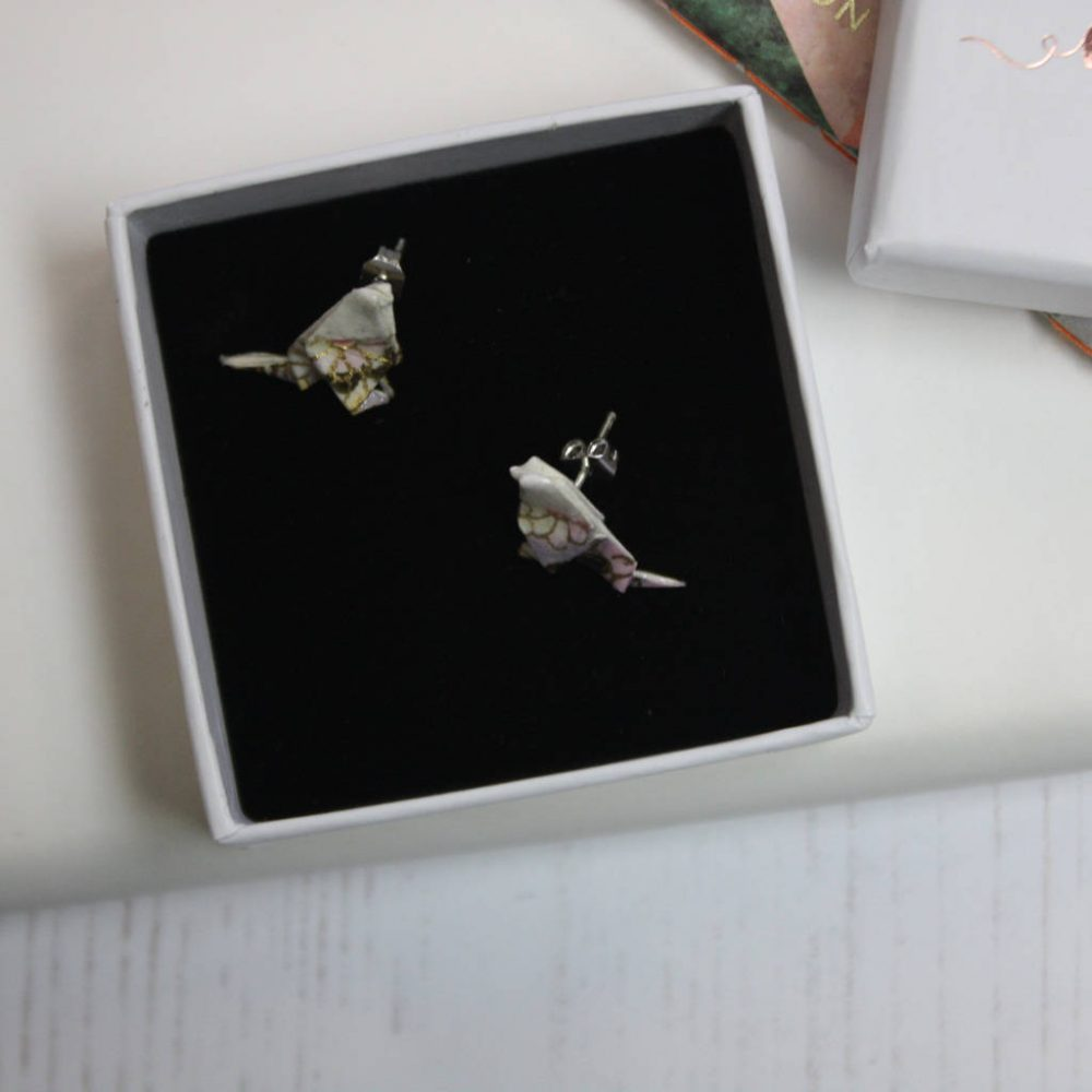 Close up of pink washi blossom bird earrings in white presentation box.