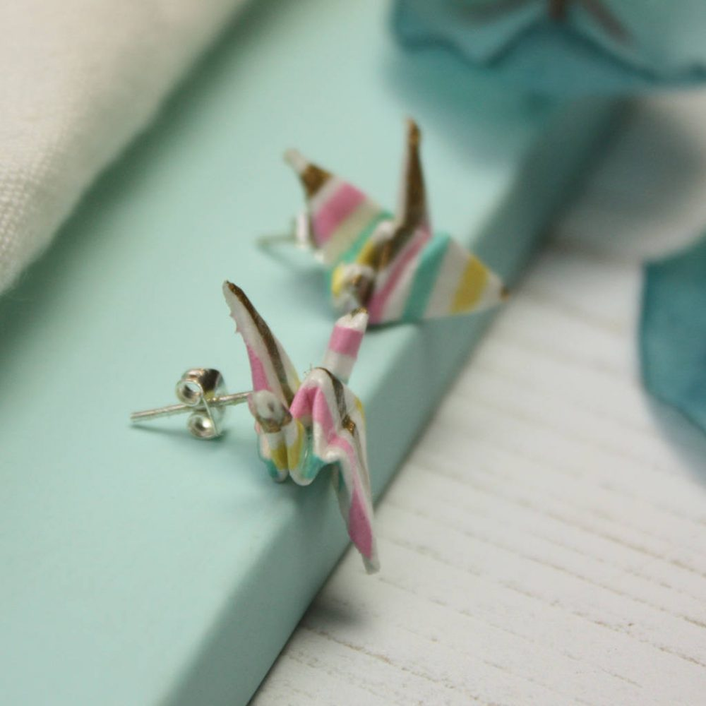 Close up of origami crane earrings, in candy stripe. Handmade by the origami boutique.