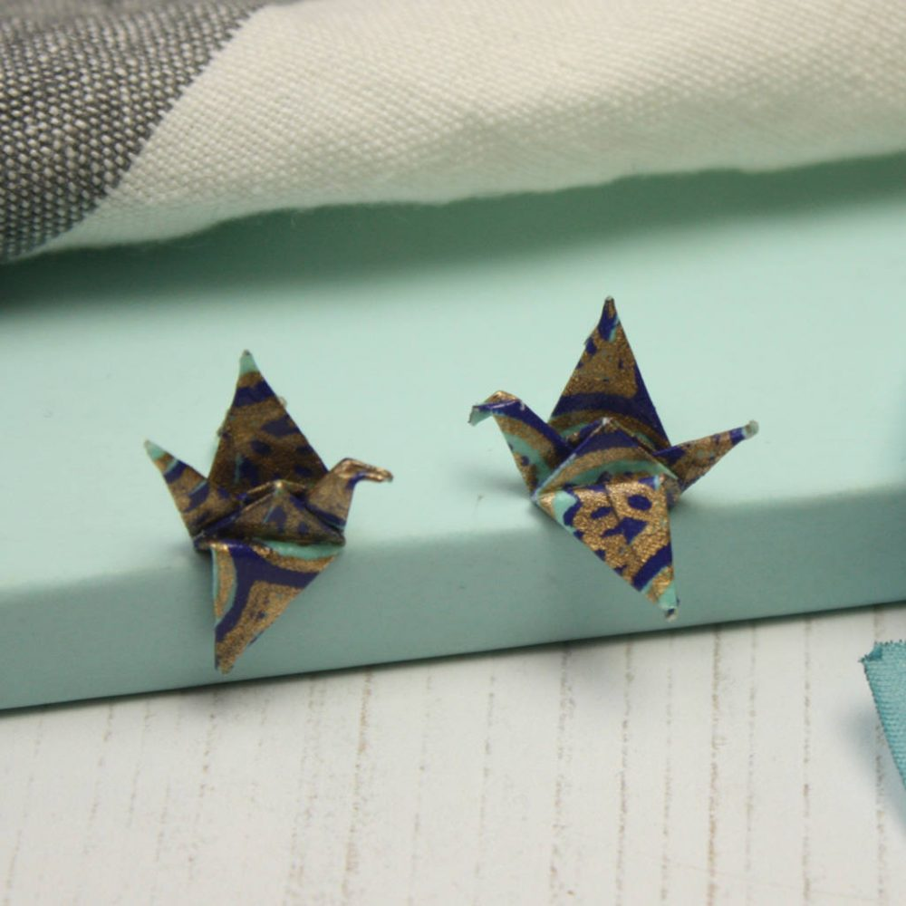 Water resistant paper origami crane earings, in blues and gold, hand folded by the origami boutique.