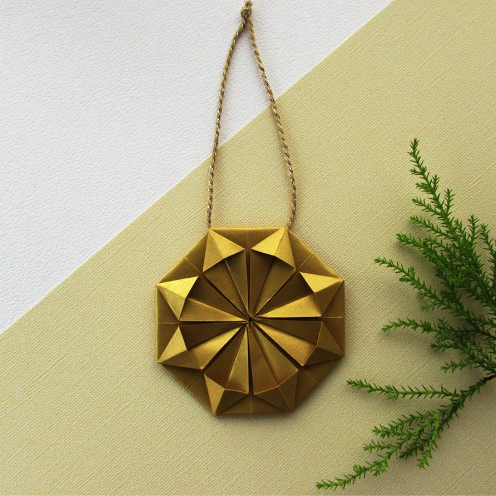 Metallic gold origami snowflake inspired christmas ornament.