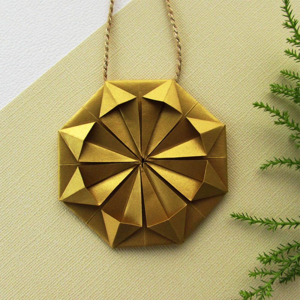 Close up of metallic gold origami snowflake inspired christmas ornament. Handmade by the origami boutique.