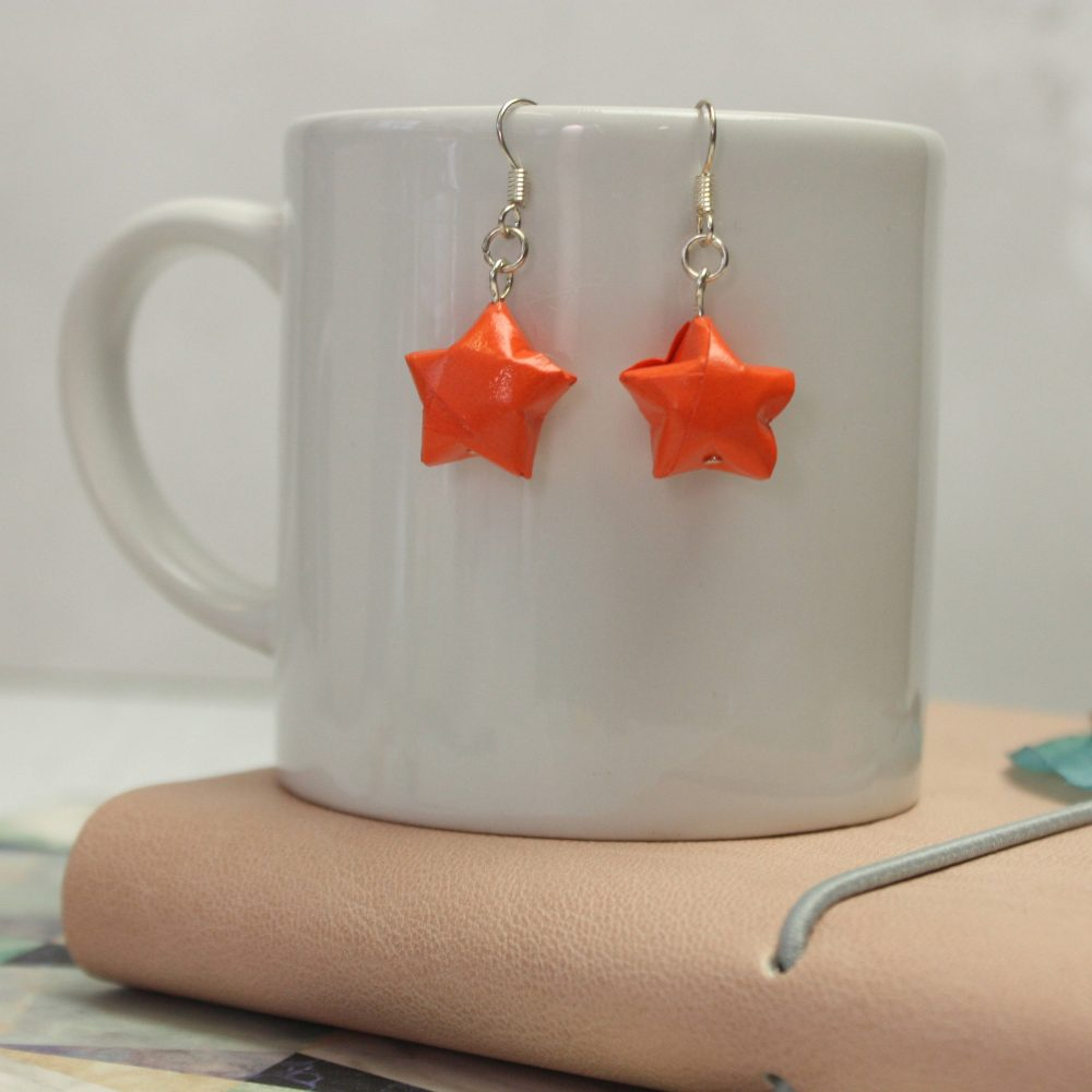 Hanging Orange star earrings. Water resistant origami jewellery, by the origami boutique, london.