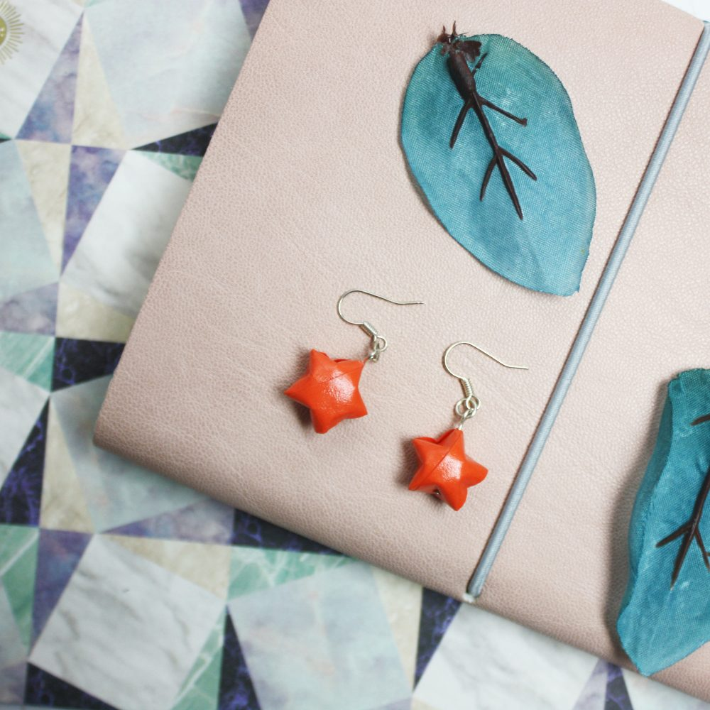 Dangling orange star earrings. Water resistant origami jewellery, by the origami boutique, london.