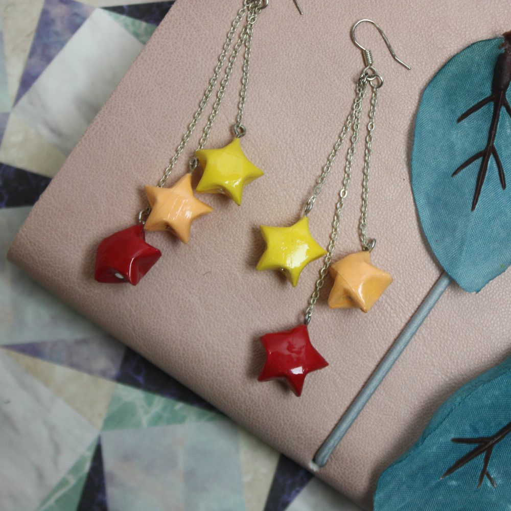 Dangling origami star earrings in yellow, orange, and red. Handmade at the Origami boutique, london.