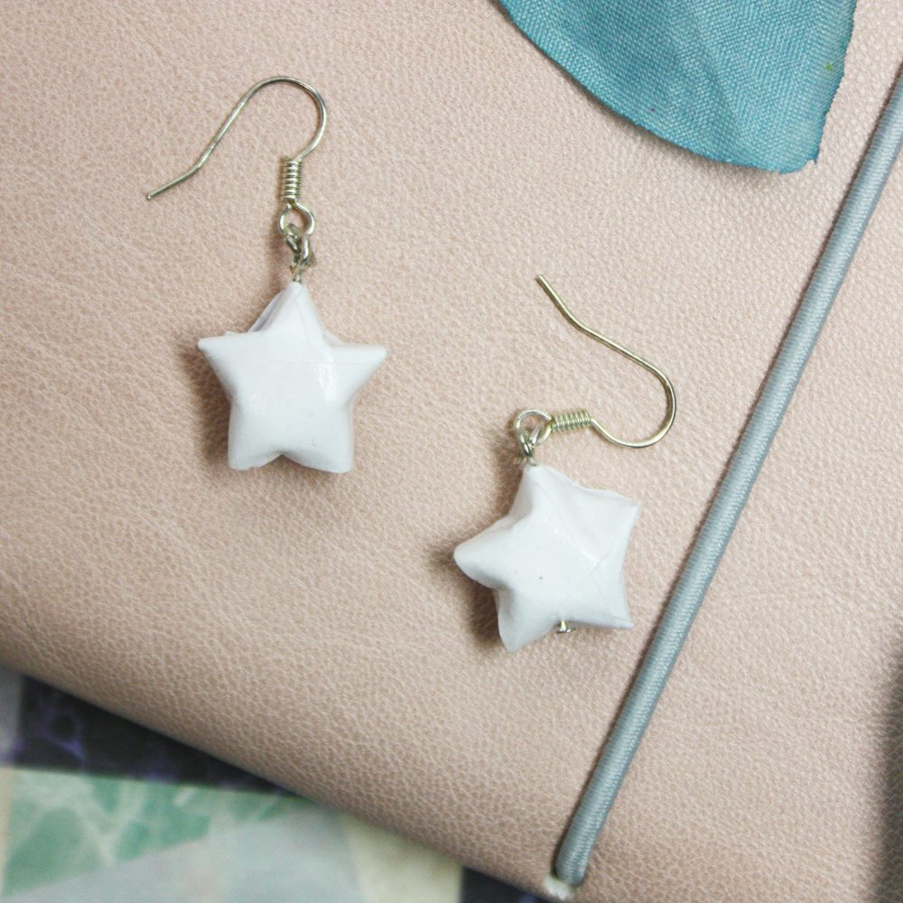 Hanging white origami star earrings. Waster resistant. Hand folded by the origami boutique, london.