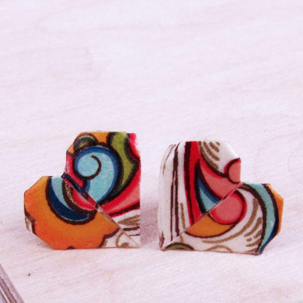 Close up of delicate origami heart stud earrings. Bright and colourful versatile jewellery.