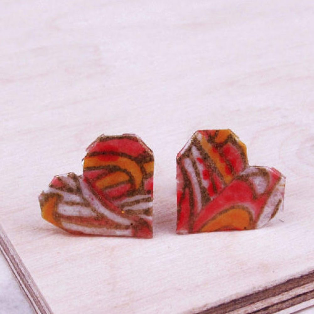Close up of origami heart earrings in salmon pink pattern, handmade by the origami boutique.