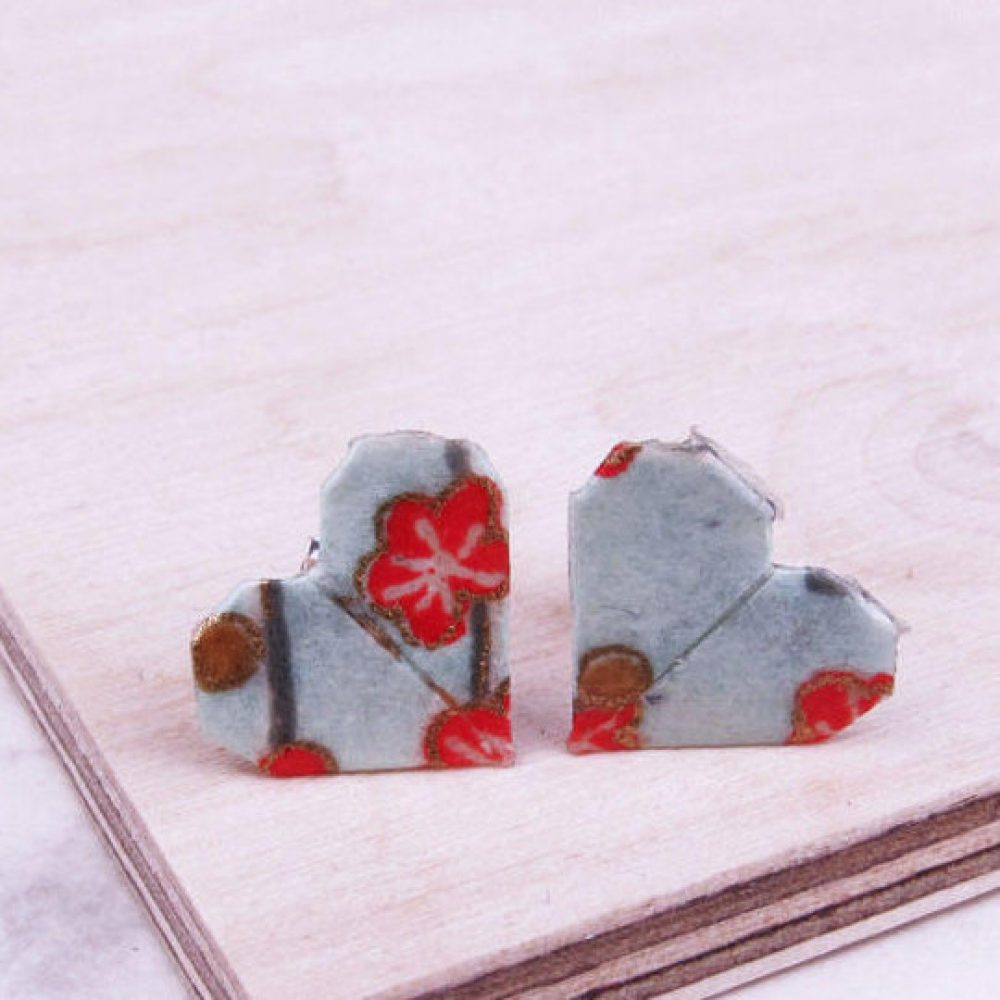 Close up of geometric heart earrings, in blue with red floral design. Versalite and water resitant, by the origami boutique.