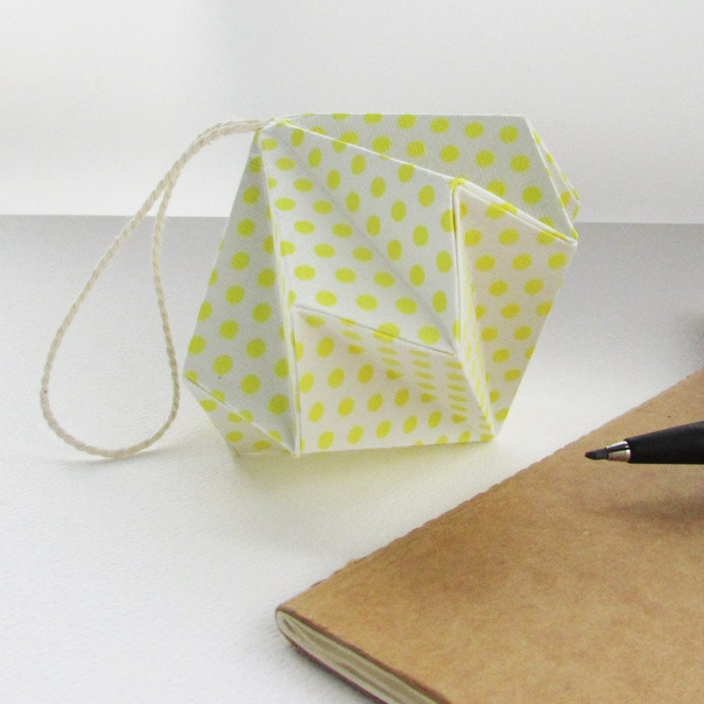 flourescent yellow polkadot on white, origami orniament. Hand folded by the origami boutique, london.
