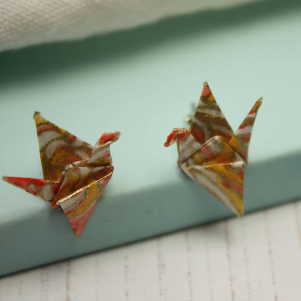 close up of the origami boutiques salmon burst crane earrings.